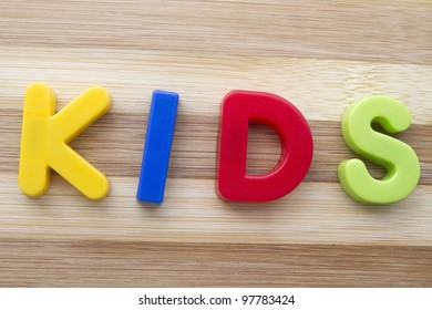 "Letter magnets ""KIDS"" closeup on wood background"