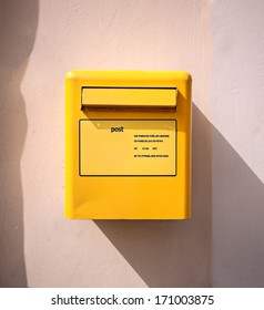 letter mail delivery post yellow box at wall