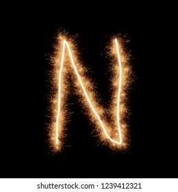 Letter N of alphabet written by squib sparks on a black background.