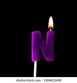 Letter N celebration birthday candle against a black background
