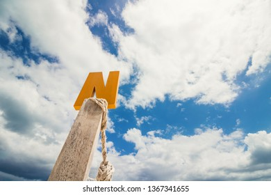 Letter N wood in front of blue cloud sky