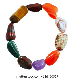 The letter O spelled with semi-precious stones against white background