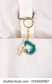Letter P Green and Gold Keychain on a White Canvas Bag