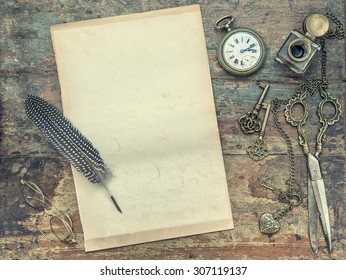 Letter paper and vintage writing tools. Feather pen, inkwell, keys on textured wooden background. Retro style toned picture