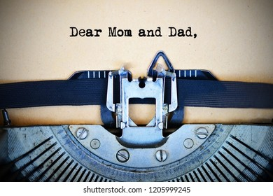 Letter for parents beginning with Dear mom and dad text typed by vintage typewriter machine