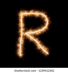 Letter R of alphabet written by squib sparks on a black background.