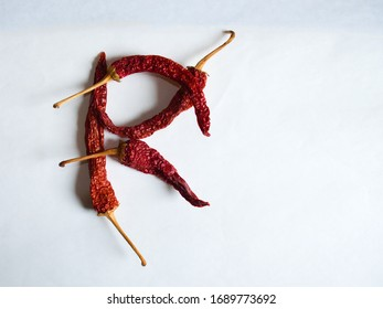 Letter R lined with red peppers on a white background. Symbol in the form of the letter R. Pepper lined in the letter R on a white background.