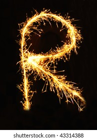 Letter R made of sparklers isolated on black