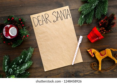 Letter to Santa Claus template. Mockup on craft paper with text Dear Santa near New Year decoration like fir branches, candle, toy horse on dark wooden background top view