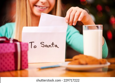 Letter to Santa. Close-up of cheerful little girl putting a letter to Santa into the envelope while sitting at the table with glass of milk and cookies laying on it