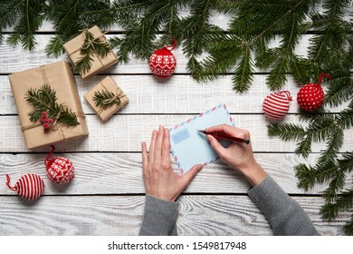Letter to Santa. Woman's hands writing address on a letter, over a frame made of green fir branches with gift boxes on white planks, flat lay
