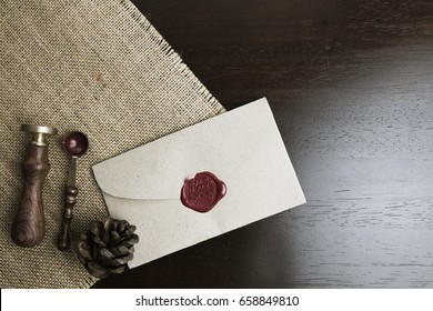 letter seal with wax seal stamp on the wood table and fabric ,  Pine cone on the fabric