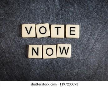 Letter tiles on black slate background spelling Vote Now
