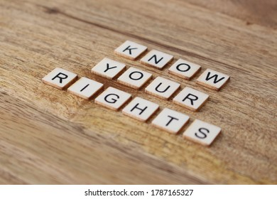 Letter tiles on wooden background spelling Know Your Rights