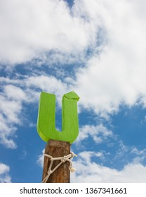 Letter U wood in front of blue cloud sky