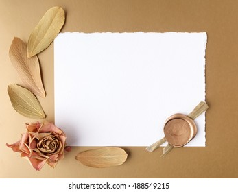 Letter with wax seal and dry roses on golden background. Flat lay. Top view