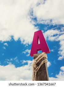 Letter A wood in front of blue cloud sky