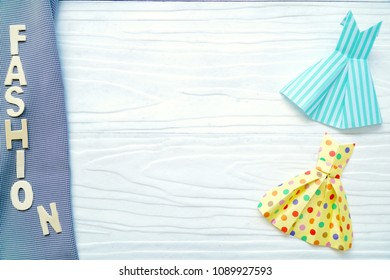"""Letter word """"Fashion"""" and cute Paper dress origami on wood background. Fashion, beauty concept. Copy space. Can be use for brochure, banner."""