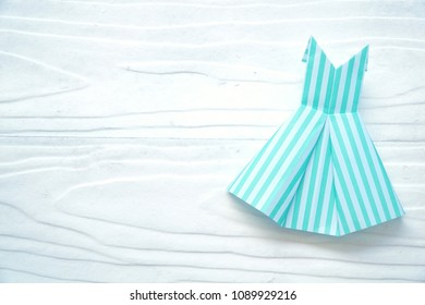 """Letter word """"Fashion"""" and cute Paper dress origami on wood background. Fashion, beauty concept. Copy space. Can be use for banner, brochure."""