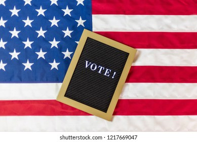 Letterboard sign with the word vote on American flag background - voting concept