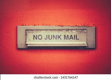 A Letterbox On A Grungy Orange Door With A No Junk Mail Sign