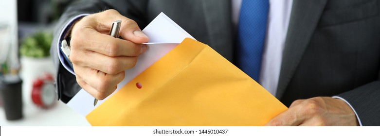Letterbox view of clerk in suit and tie at workplace packing envelope unpacking envelope with important documentation close-up