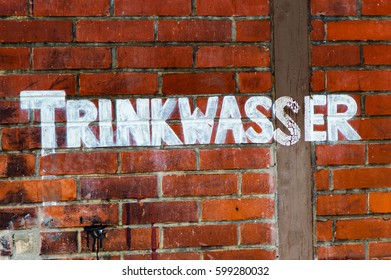The Lettering drinking water painted on a stone wall