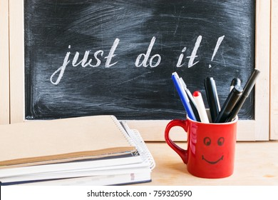 Lettering of phrase JUST DO IT on black chalkboard on a background of notepads and diary and a red cup with a cheerful smile. Procrastination, motivation concept.  Self-control and achieving the goal
