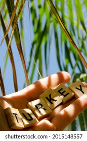 Lettering Turkey on hand against background of blurred turquoise sea, blue sky and palm leaves. Inscription Turkey. Sea vacation concept. Representation of country resorts. - Shutterstock ID 2015148557