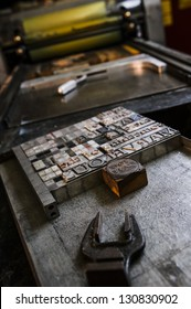 Letterpress type in foreground and printing press in the background