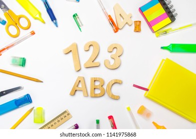 letters A, B, C. numbers 1, 2, 3 on the school desk. concept of education. back to school. stationery. White background. stickers, colored pens, pencils, scissors. view from above. flat lay.