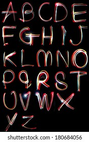 the letters, a,b,c,d,e,f,g,h and i written in the dark with torches and lasers