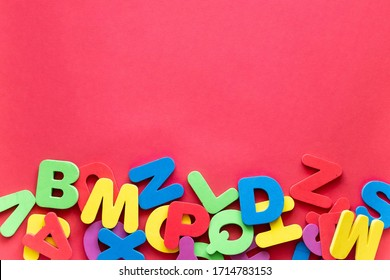 Letters of The Alphabet in Different Colors on a Red Background. Alphabet Study, ABC, Education Concept