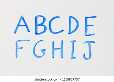 the letters A B C D E F G H I J in blue marker on a dry erase white board