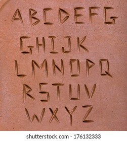letters carved on clay