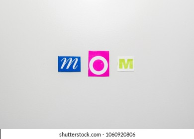 """letters cut out from newspapers and magazines that form the word """"mom"""", on a light gray background"""