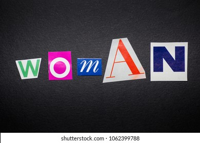 """letters cut out from newspapers and magazines that form the word """"woman"""", on a black background"""