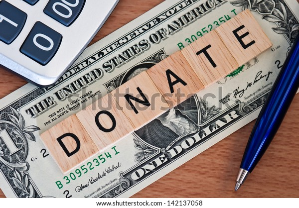 The letters DONATE on  dollar banknote business concept