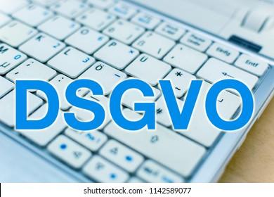 Letters DSGVO (blue color) in front of Laptop Keyboard, German: Datenschutzgrundverordnung