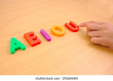 Letters a e i o and u and a child hand. School concept