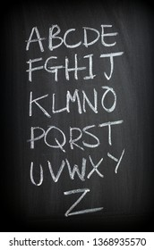 The letters of the entire English Alphabet written by hand in white chalk on a blackboard