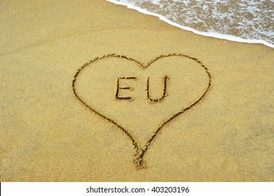 The letters EU framed by a heart at the beach