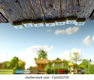 Letters of freedom from a plastic word puzzle on a mole and reflections on some houses and trees on a pond, upside down