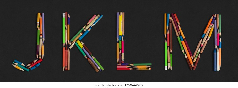 Letters: J K L M, alphabet made from colorful used pencils, on dark grey cardboard background. Very high letter size (about ~25cm/300dpi).