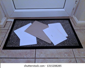 Letters on a blue doormat on a tiled floor in front of a white door, just posted through the letterbox
