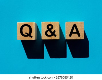 The letters Q and A A wooden cube on a turquoise background Concept, question and follow
