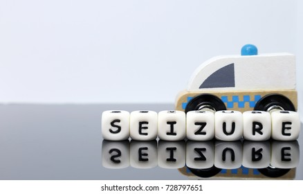 letters spelling a word seizure in front of a model ambulance on a reflecting background, emergency, rapid response, serious medical condition, conceptual idea