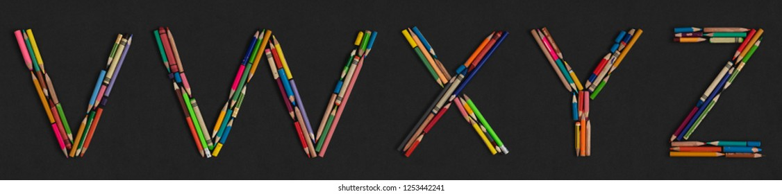 Letters: V W X Y Z, alphabet made from colorful used pencils, on dark grey cardboard background. Very high letter size (about ~25cm/300dpi).