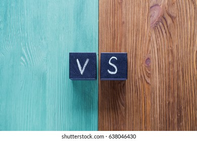 Letters VS on wooden background with copy space. The concept of making choice.  Versus letters. Turquoise and brown wooden background and black cubes with letters VS.