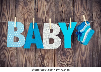 letters of word baby and knitted socks hanging on clothesline against wooden background